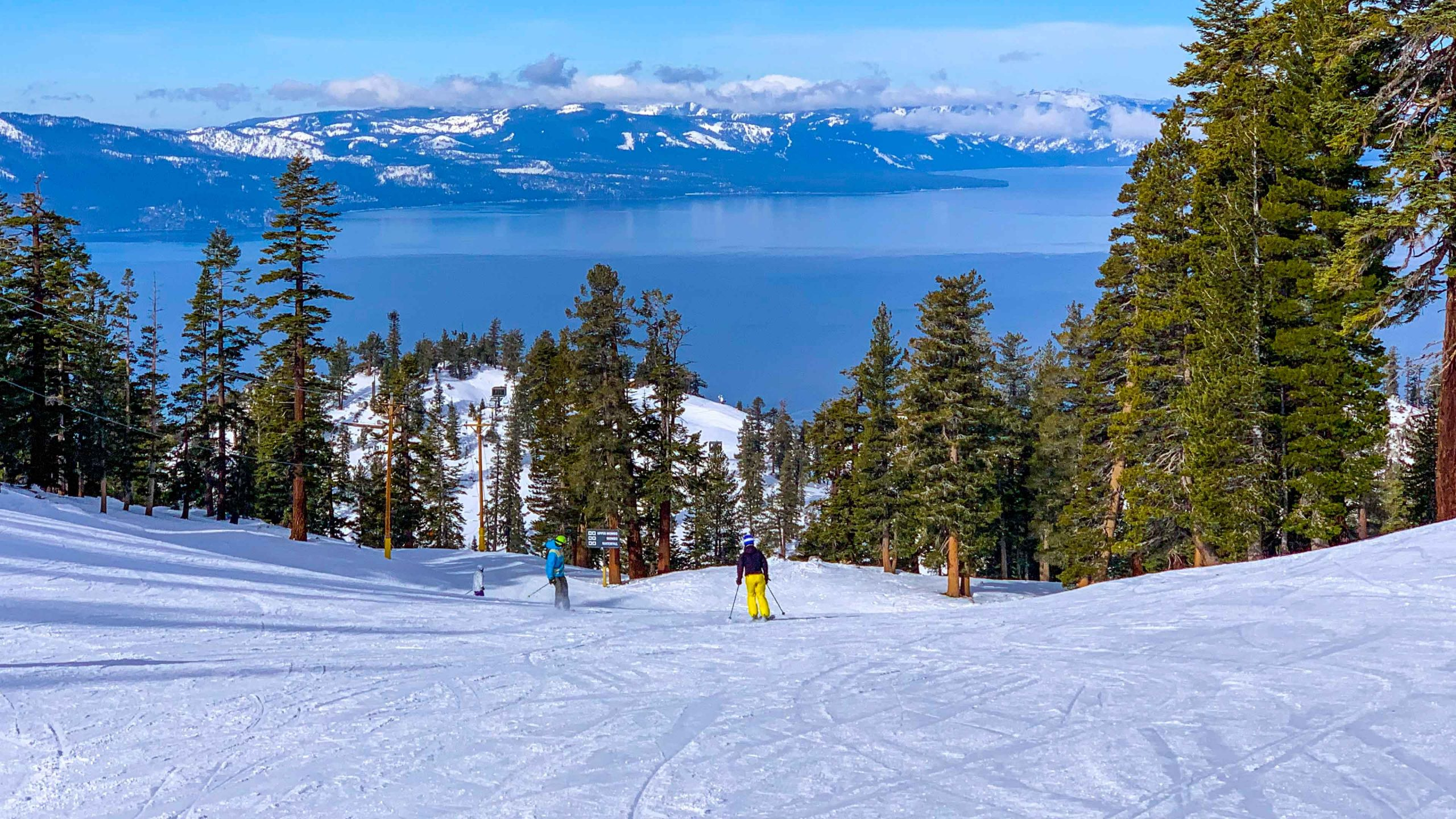 View downhill at ski resort with Lake Tahoe in background.