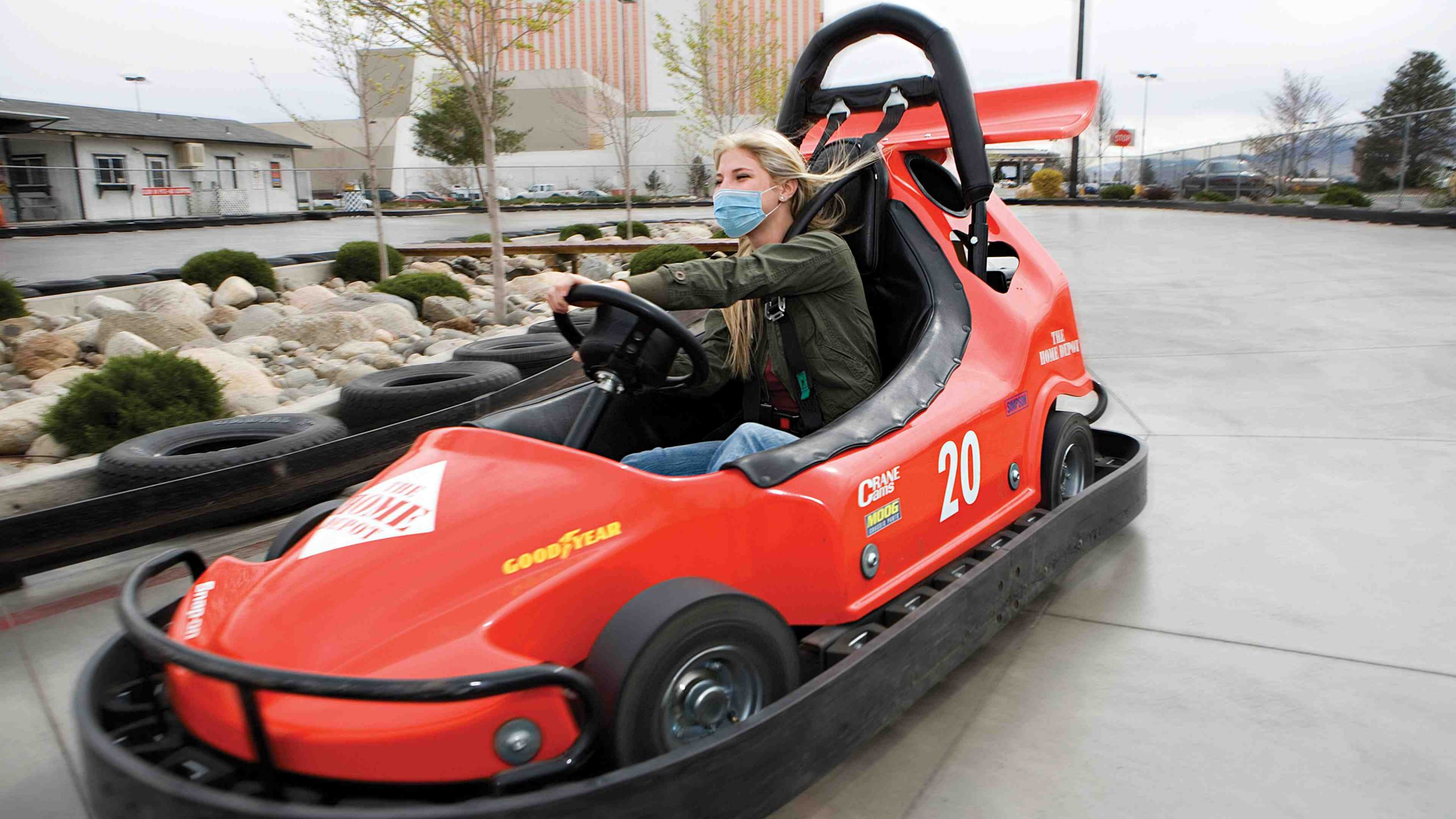 Lady in a mask taking a turn in a red go-kart