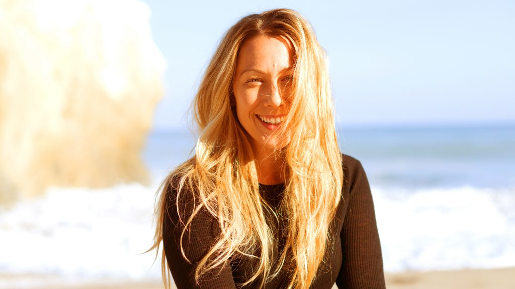 Colbie Caillat posing in front of waves crashing in the background