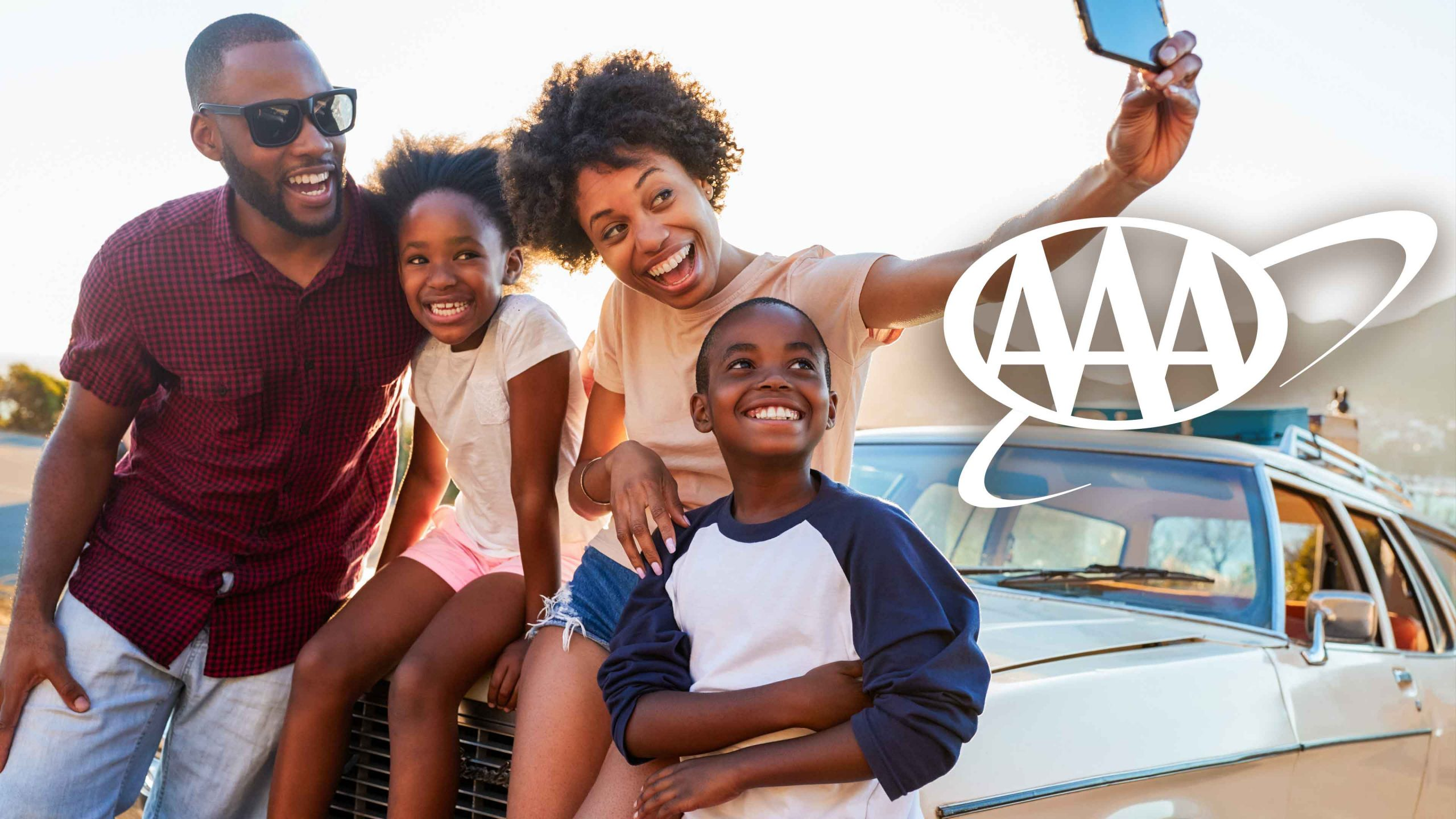 Young family on road trip taking selfie with AAA logo