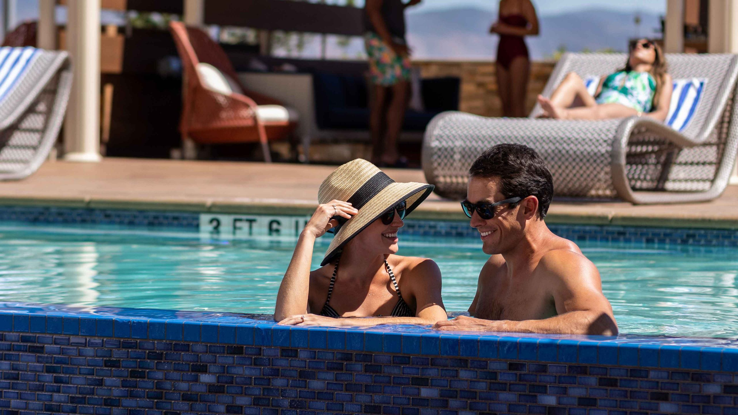 Couple in Infinity Pool with Cabanas in background.